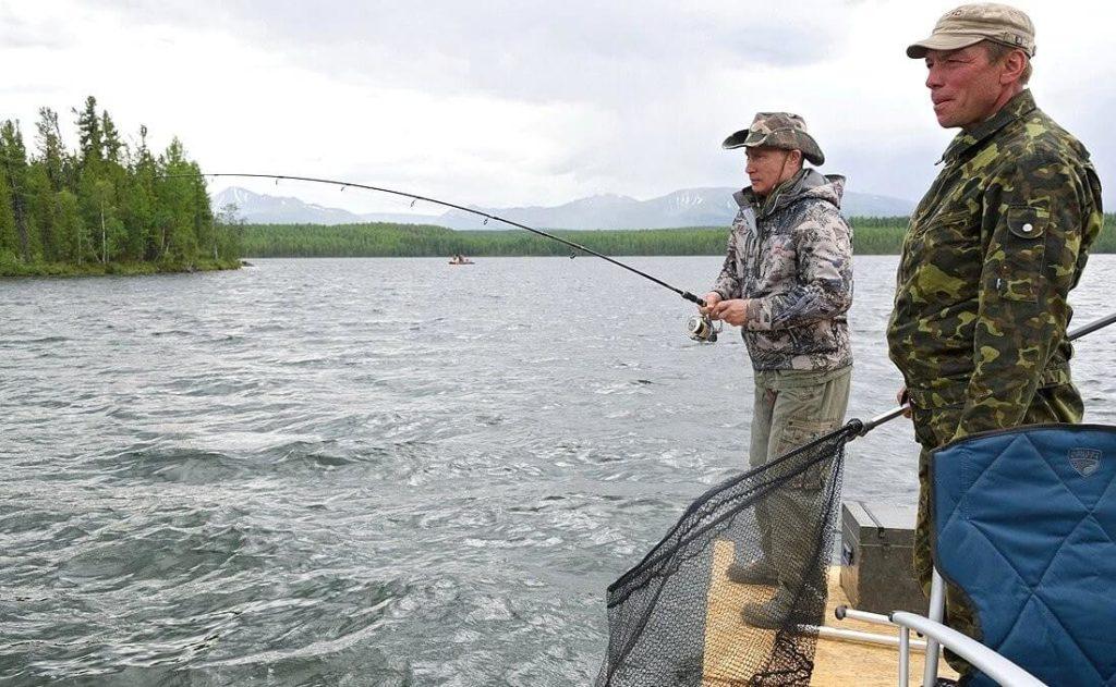 Der russische Präsident mit Fisch im Drill beim Angeln